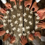 Afbeelding waarop meerdere handen een puzzel leggen