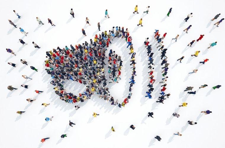 Een afbeelding met hierop mensen die staan in de vorm van een megafoon