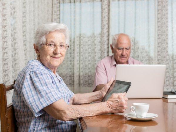 Een afbeelding met hierop twee oudere mensen achter een laptop en tablet
