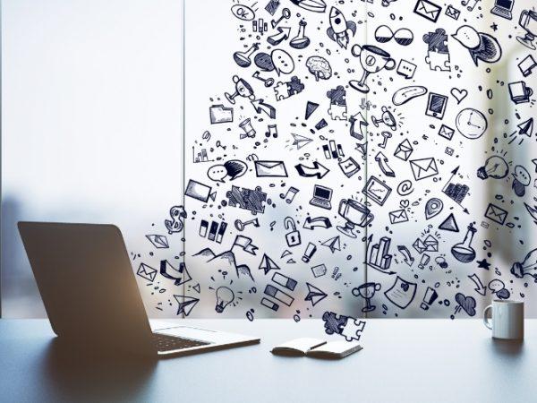 Een afbeelding met hierop een Macbook, notitieblok en symbolen voor communicatie